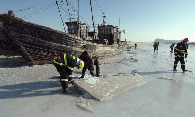 Investigators inspect a port where ships are stranded in ice, in Jinzhou, Liaoning province, January 5, 2013. (c) REUTERS/China Daily