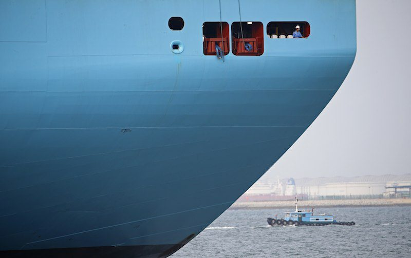 A crew member looks out from the MV Maersk Mc-Kinney Moller as it berths during its maiden port of call at a PSA International port terminal in Singapore