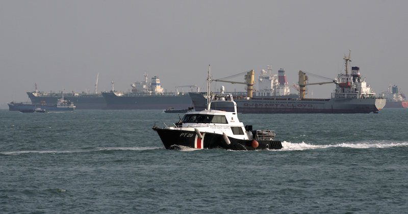 A Police Coast Guard vessel patrols the shipping lanes near freight ships off the coast of Singapore in this March 4, 2010 file photo.  REUTERS/Vivek Prakash/Files