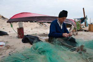Palestinian fisherman mends his nets